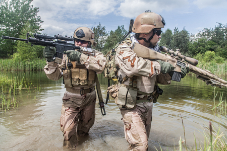Foto de Navy SEALs crossing the river with weapons - Imagen libre de derechos