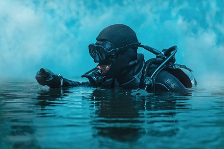 Foto de Navy SEAL frogman with complete diving gear and weapons in the water - Imagen libre de derechos