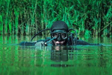 Foto de Navy SEAL frogman with complete diving gear and weapons in the water - Imagen libre de derechos