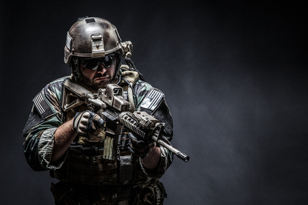 Photo pour United states Marine Corps special operations command Marsoc raider with weapon. Studio shot of Marine Special Operator half-turning black background - image libre de droit