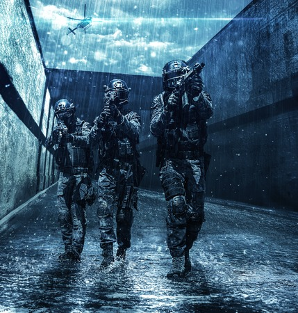 Foto de Police squad moving across sewer tunnel during mission. Police helicopter supporting from air. Raining cloudy weather, they are wet and drenched - Imagen libre de derechos