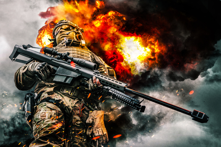 Foto de Army sniper of special forces in action posing with large caliber rifle. Heavy explosions, fire and smoke billowing on background. Low angle view - Imagen libre de derechos