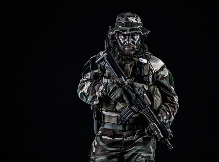 Foto de Bearded Special forces United States in Camouflage Uniforms studio shot half length black background. Holding weapons, wearing jungle hat, Shemagh scarf, he is ready to kill. Backlit - Imagen libre de derechos