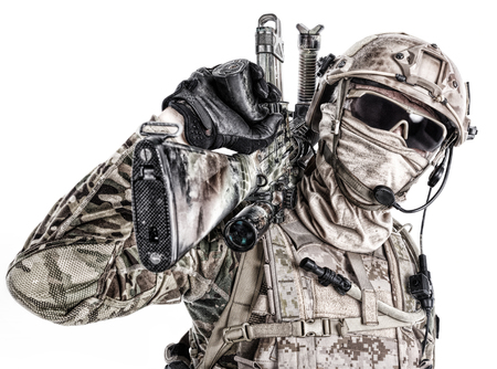 Foto de Half length low angle studio shot of special forces soldier in field uniforms and face mask with sniper rifle on his shoulder, portrait isolated on white background - Imagen libre de derechos