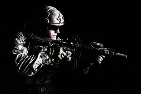 Foto de Half length low angle studio shot of special forces soldier in field uniforms with weapons, portrait on black background. Protective goggles glasses are on - Imagen libre de derechos