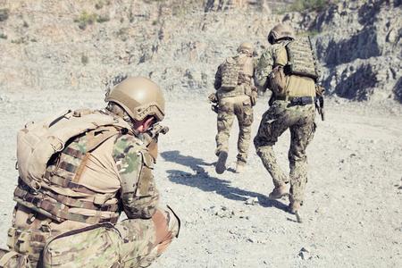 Foto de Team squad of special forces in action in the desert among the rocks - Imagen libre de derechos