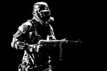 Foto de Futuristic nazi soldier gas mask and steel helmet with schmeisser handgun black background studio shot - Imagen libre de derechos