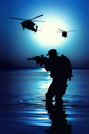 Foto de Army soldier with rifle night moon silhouette under cover of darkness in action during raid crossing river in the water. - Imagen libre de derechos