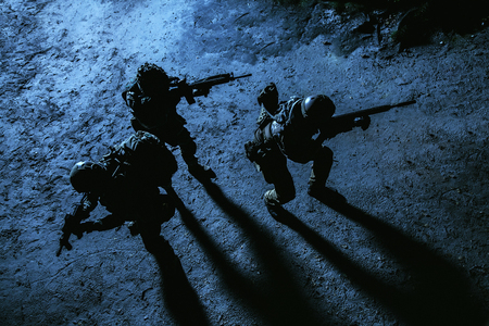 Photo pour Black silhouette of soldiers at night. View from above, toned and colorized. Squad in action - image libre de droit