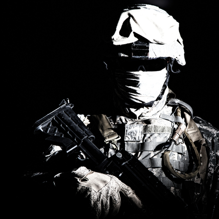 Foto de Shoulder portrait of war, military conflict combatant, army special forces soldier, counter terrorist forces fighter armed with rifle in combat helmet, glasses and mask cropped on black background - Imagen libre de derechos