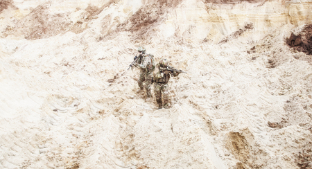 Foto de Two infantry soldiers in combat camo uniform, with tactical ammunition, carefully walking and aiming with assault rifles in unknown desert area. Military reconnaissance, scouting on enemy territory - Imagen libre de derechos