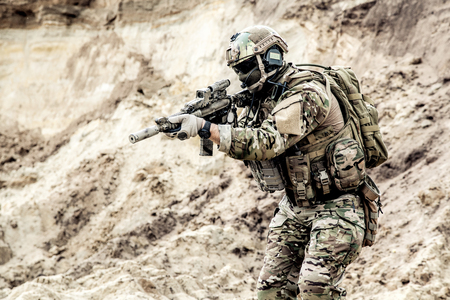 Foto de Army infantryman, special forces soldier with hidden face, protected opscore helmet and body armor, equipped tactical radio headset, in ocp camouflage uniform, aiming with service carbine in hands - Imagen libre de derechos