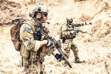 Foto de Two armed US army commandos or military scouts equipped with radio headset moving forward in sands during enemy area reconnaissance. Special forces operation, long range surveillance mission in desert - Imagen libre de derechos