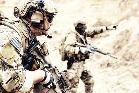 Foto de US special operations forces fighters armed with assault rifle, in opscore helmet, radio tactical ops headset, moving forward with caution in desert. Reconnaissance by fire in zone of war conflict - Imagen libre de derechos