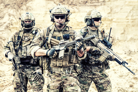Foto de Group portrait of US army elite members, private military company servicemen, anti terrorist squad fighters standing together with guns. Brothers in arms, war conflict combatants, soldiers of fortune - Imagen libre de derechos