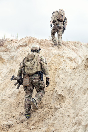 Foto de Two modern infantry, special operations forces soldiers, military intelligence specialists armed with service rifles in protective camouflage uniform with backpack on backs climbing on sand dune - Imagen libre de derechos