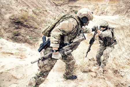 Foto de US ranger, modern infantryman, special reconnaissance team member or military scout in ammunition, armed with service rifle helping brother in arms to climb on sand dune. Army brotherhood and teamwork - Imagen libre de derechos
