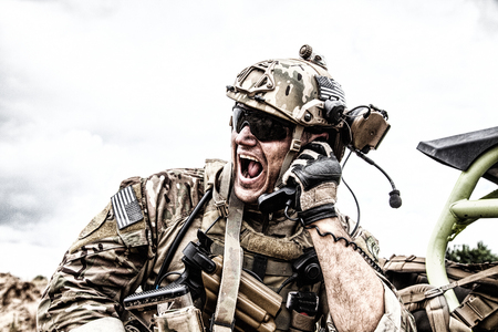 Foto de Special forces soldier, military communications operator or maintainer in helmet and glasses, screaming in radio during battle in desert. Calling up reinforcements, reporting situation on battlefield - Imagen libre de derechos