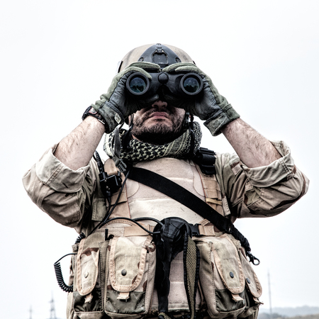 Foto de Special operations forces soldier, Navy SEAL scout in battle uniform and helmet, looking through binoculars, observing area, searching targets, monitoring enemy movements, directing artillery fire - Imagen libre de derechos