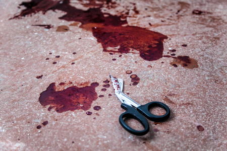 Photo for Trauma shears or bandage scissors lying on floor with stains of human blood around. Blood loss and bleeding stop, emergency medical aid for gunshot wounds, tactical combat casualty care on battlefield - Royalty Free Image