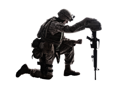 Foto de Army soldier in sorrow for fallen comrade, standing on knee, leaning on rifle with helmet and two dog tags on chain, studio shoot isolated on white low key silhouette. Military funeral honors, grief for killed in action - Imagen libre de derechos