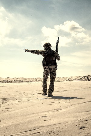 Foto de Soldier of special forces, infantry rifleman in military ammunition walking in desert and pointing on horizon. Military reconnaissance team leader managing dead ground observation with combat patrol - Imagen libre de derechos