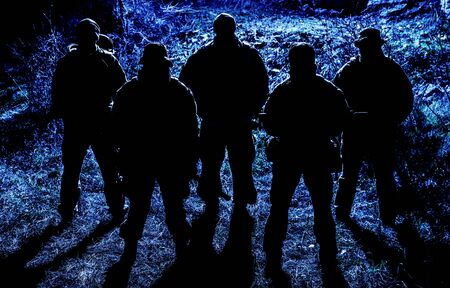 Foto de Group of armed soldiers, modern military mercenaries, secret service fighters, army special operations riflemen, commandos crew standing together in line in darkness, patrolling area at nighttime - Imagen libre de derechos