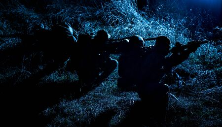 Foto de Commandos group, army special operations tactical group, military patrol team marching in field loaded with ammunition, sneaking in darkness, carefully and quiet moving in line during night mission - Imagen libre de derechos
