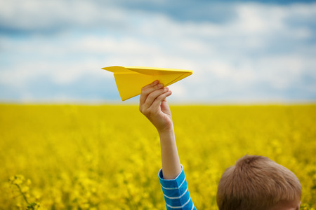 Foto de Paper airplane in children hands on yellow background and blue sky in coudy day - Imagen libre de derechos