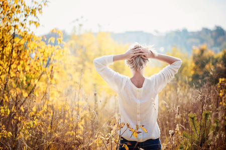 Photo for Happy young girl enjoying the beauty of sunny autumn day  in high grass in an autumn park. View from a back. - Royalty Free Image