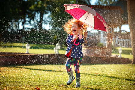 Foto de Very Happy Little girl with umbrella playing in the rain. Kids play outdoors by rainy weather in fall. - Imagen libre de derechos