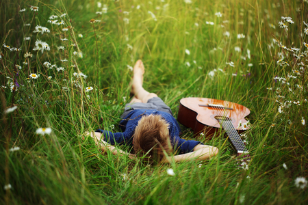 Photo for Teenage boy lying on grass with his acoustic guitar. - Royalty Free Image