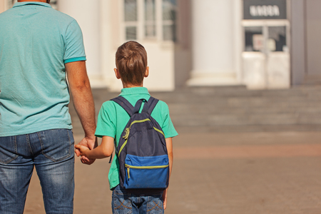 Foto de Cute little boy with backpack going to school with his father. Back view - Imagen libre de derechos