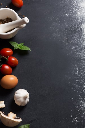 Photo pour Baking background with copy space on black surface for your text. Flour and vegetables are traditional ingredients for breadmaking and other baking. Often used in mediterranean cuisine - image libre de droit