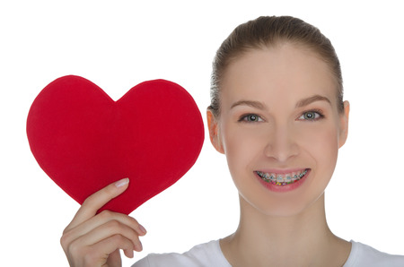 Foto de Happy girl with braces on teeth and red heart isolated on white - Imagen libre de derechos
