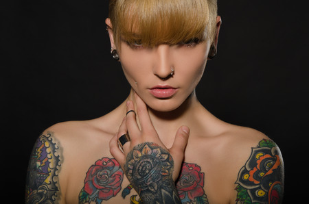 Photo pour Beautiful blonde with a tattoo on body, dark background - image libre de droit