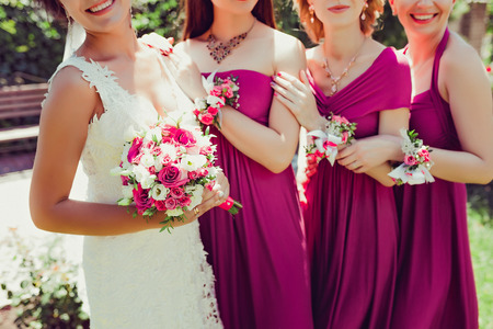 Photo for Row of bridesmaids with flowers on hands, holding each other - Royalty Free Image