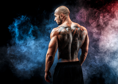 Photo pour Bald unrecognizable tattooed man with strong muscles posing, resting in smoke. Looking sideways - image libre de droit