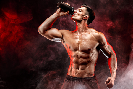 Photo for Muscular man with protein drink in shaker over dark smoke background - Royalty Free Image