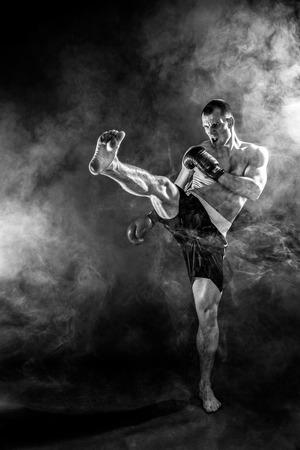 Foto de Muscular kickbox or muay thai fighter punching in smoke. - Imagen libre de derechos