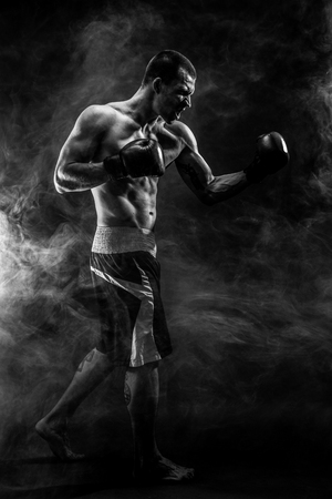 Photo for Muscular kickbox or muay thai fighter punching in smoke. - Royalty Free Image