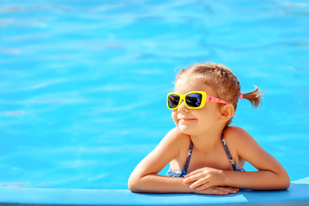 Photo pour Smiling cute little girl in sunglasses in pool in sunny day. - image libre de droit