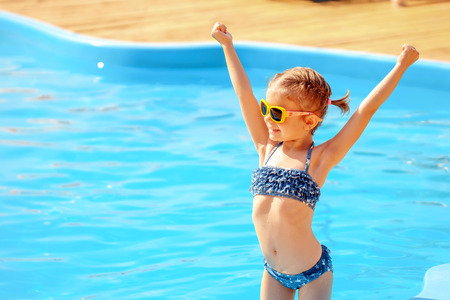 Photo pour Summer vacation concept. Little cute girl in sunglasses holding hands up near a swimming pool. - image libre de droit