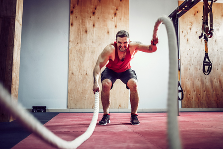 Photo for Men with battle rope in functional training fitness gym - Royalty Free Image