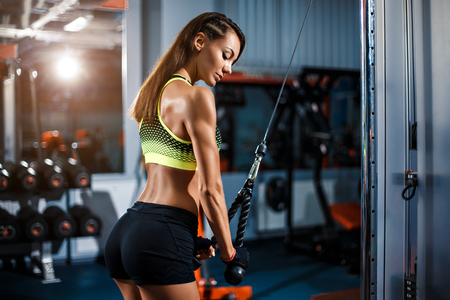 Foto de Fit well-trained blonde woman workout triceps lifting weights in gym - Imagen libre de derechos
