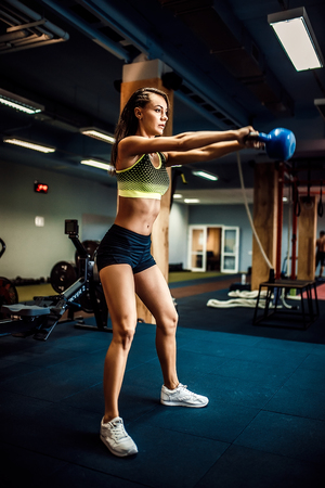 Photo for Attractive female athlete performing a kettle-bell swing in crossfit gym. - Royalty Free Image