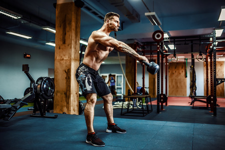 Photo pour Fitness Kettlebells swing exercise bearded man workout at gym - image libre de droit