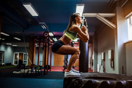 Foto de Fit young woman jumping on tire at a crossfit style gym. Female athlete is performing jumps - Imagen libre de derechos