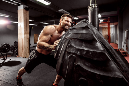 Foto per Shirtless man flipping heavy tire at crossfit gym - Immagine Royalty Free