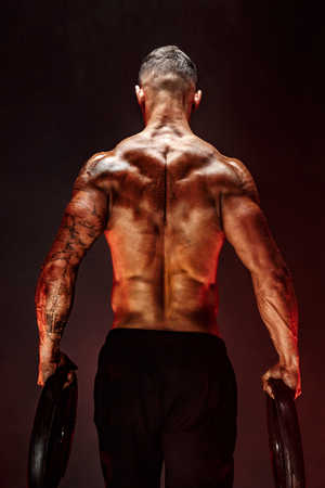 Photo for The back view of torso of attractive male body builder with dumbbells on dark smoky background. - Royalty Free Image